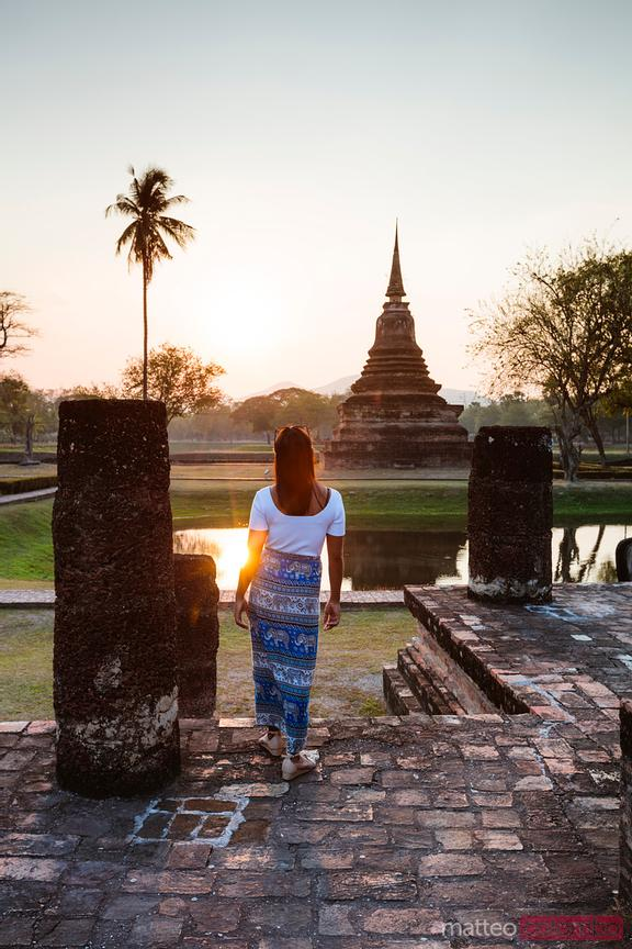Woman looking at sunset, Sukhothai Historical Park, Thailand