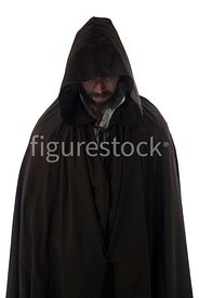 A mystery man in a big cloak standing and looking down – shot from eye level.