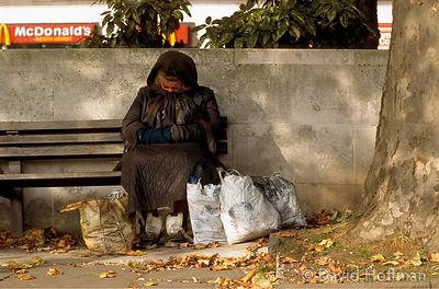 Homeless woman with bags and bundles of possessions on public bench in Hyde Prk, London, UK.