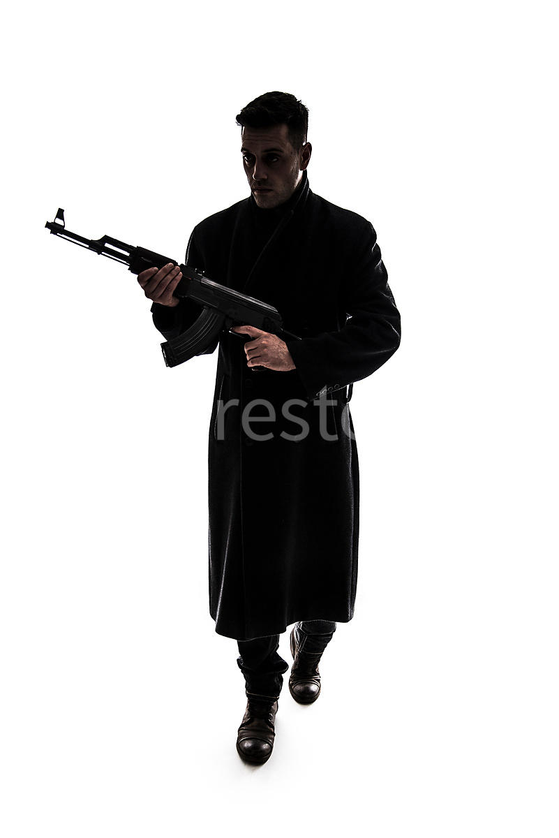 A silhouette of a mystery man, in a long coat, holding an AK-47 – shot from eye level.