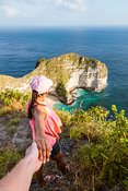 Woman holding man hand at T-rex beach, Nusa Penida, Bali