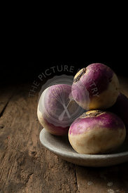 Raw turnips in a bowl on a rustic wooden surface.