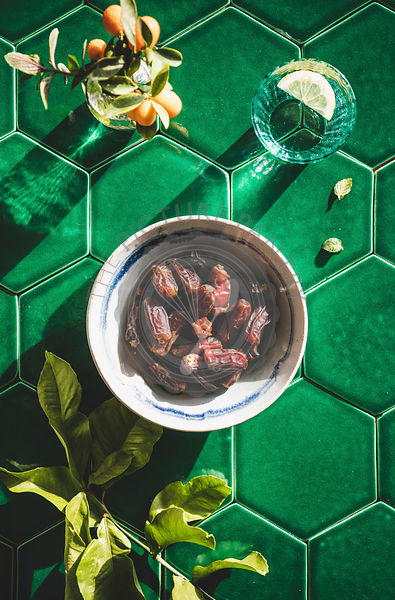 Flat-lay of Islamic Ramadan Iftar food over green tile