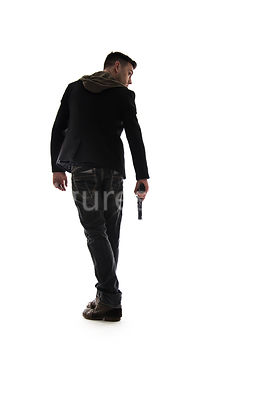 A Figurestock image of a man with a gun, in semi-silhouette, walking away – shot from low level.