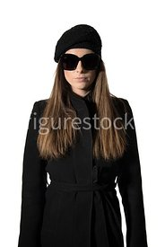 A mystery woman in coat, hat and suglasses – shot from eye level.