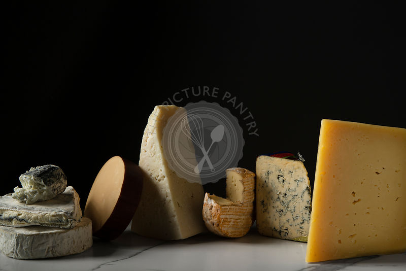 A selection of cheeses on a marble tile surface.