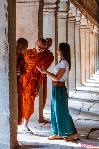 Woman talking with three buddhist monks in a  temple
