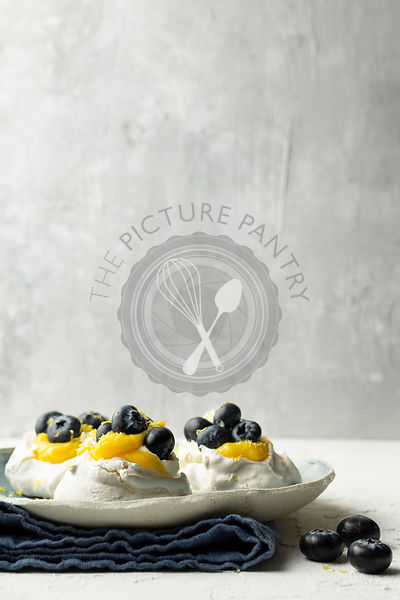 Meringues with lemon curd and blueberries on a hand-made plate, resting on a blue linen napkin.