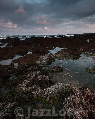 Beautiful dawn scene on rocky beach during low tide in Freshwater West, Pembrokeshire, South Wales,UK.