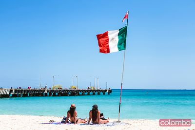 Women at the beach near mexican flag, Mexico