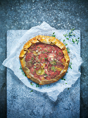 Mixed tomato tart against a blue bakground