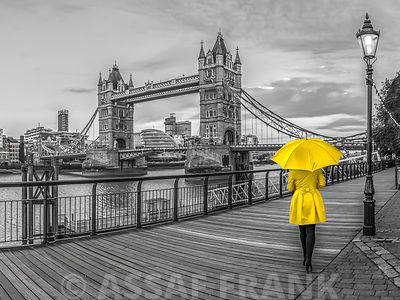 Tourist with red umbrella on promenade near Tower bridge, London, UK