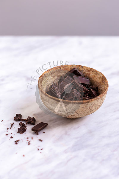 Chocolate chunks in a small ceramic bowl