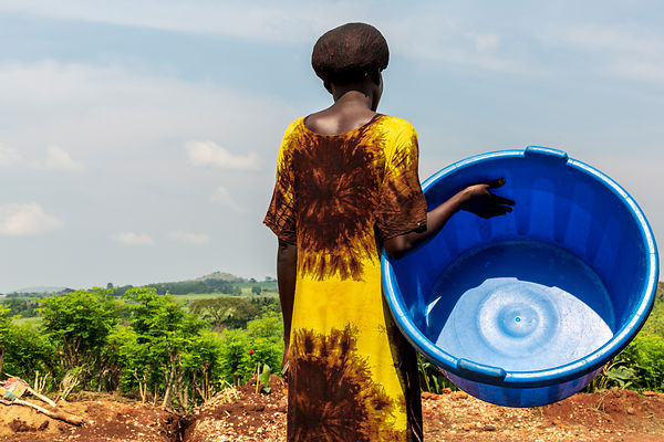 A woman and a blue washing bowl on a farm, Masindi.