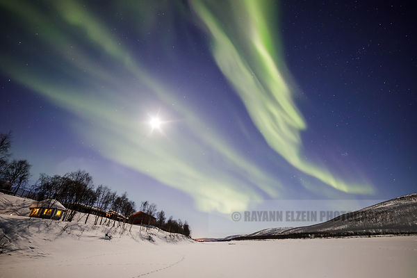 Northern lights above cottages on the frozen Tenojoki river in Utsjoki, Finnish Lapland
