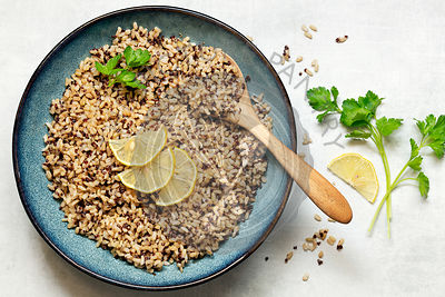 Brown rice and quinoa in a serving bowl garnished with lemon slices and parsley.