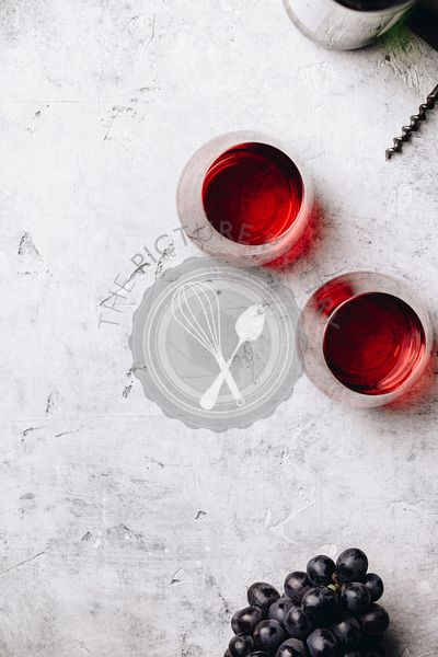 Glasses of red wine and grapes on rustic concrete background