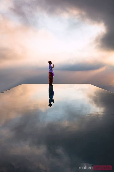 Local woman praying at sunset, reflected into water, Bali