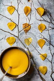 Homemade pumpkin soup in bowls and autumn leaves