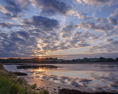 Sunrise over calm River Clyst as it joins the Exe estuary at Topsham, Devon, UK
