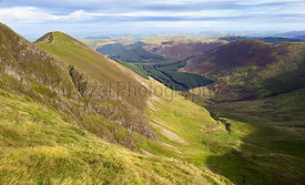 The summit of Ladyside Pike and valley of Hobcarton Plantation on a sunny day in the Lake District, England, UK.