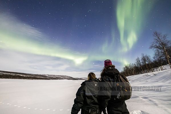 Two tourists enjoy the northern lights in Utsjoki, Finland