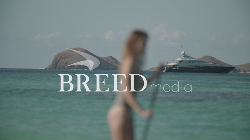 BMS001_023_HD_25fps_Woman_on_Paddleboard_with_Yacht_in_distance