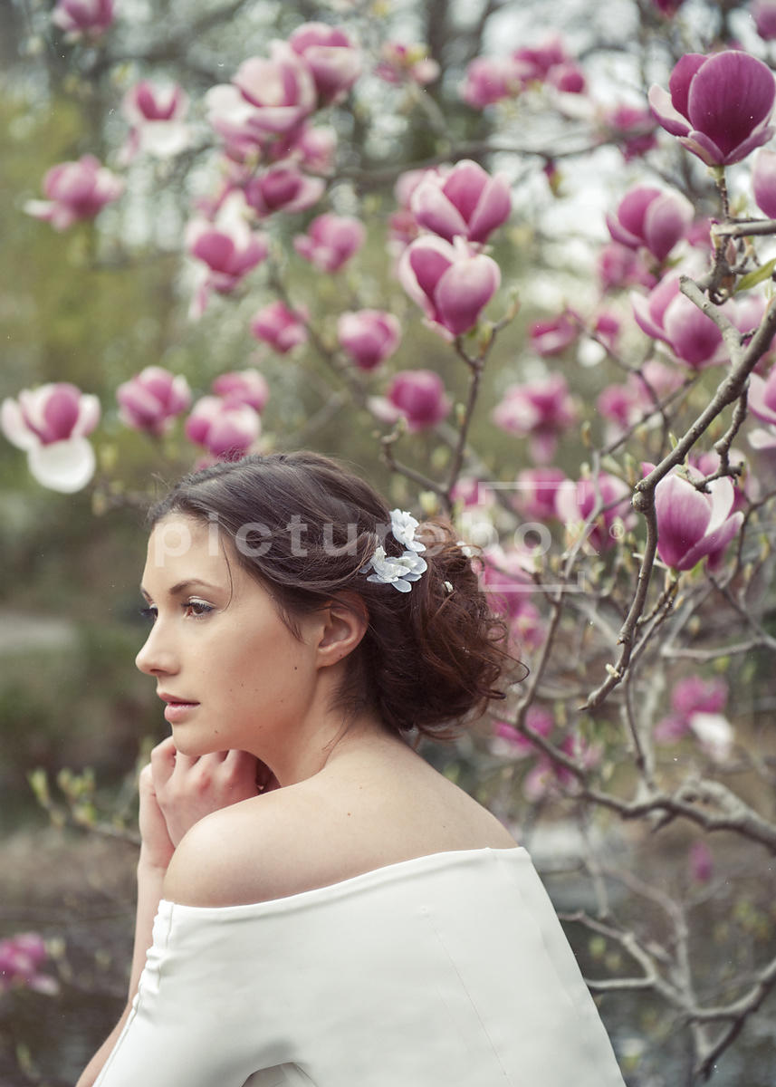 An atmospheric image af a woman in a white dress, sitting by a magnolia tree.