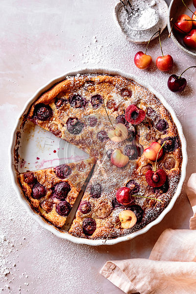 Cherry clafoutis in a flan dish with a slice cut.