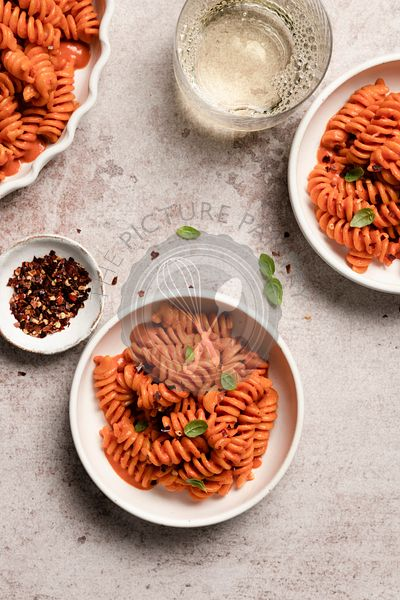 Bowls of roasted red pepper pasta with a glass of white wine.