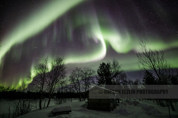 Wooden shed under a strong display of the northern lights in Kaamanen in Lapland (Finland)