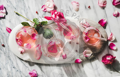 Rose lemonade with ice cubes and fresh rose petals