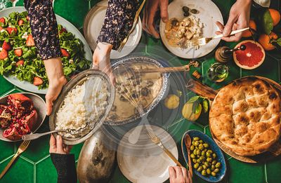 People passing Turkish foods over celebration dinner table, top view