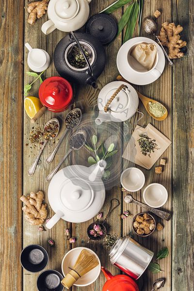 Various tea and teapots composition, dried herbal, green, black tea and matcha tea on wooden table background
