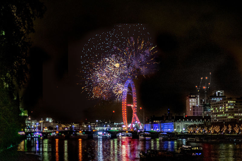 FIreworks on the London Eye celebrating the start of 2019 with lights reflecting in the waters of the River Thames