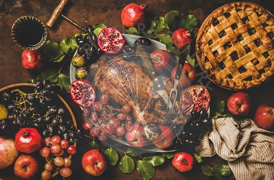 Flat-lay of roasted duck, pie, wine and fruits for Thanksgiving