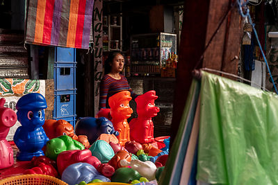A woman passes a stall selling colourful toys inside the Mercado Terminal