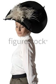 An Edwardian woman in a big hat, standing and looking down – shot from eye-level.
