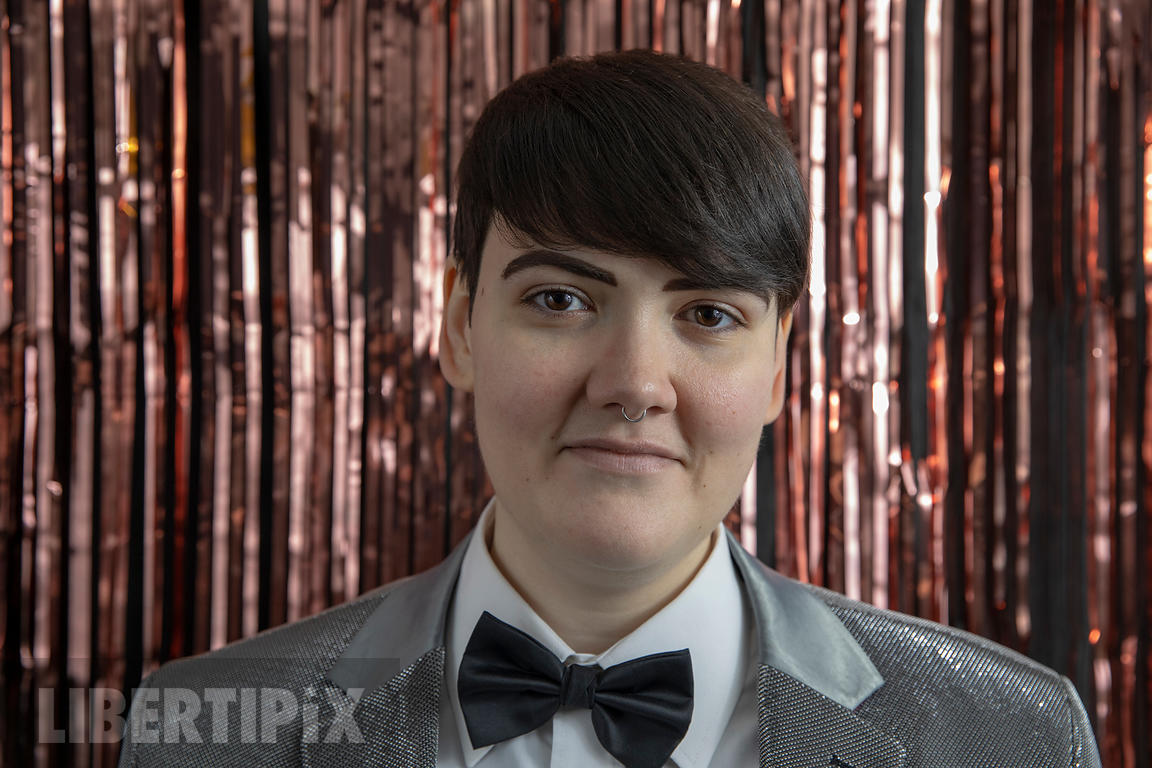 A NON-BINARY PERSON IN FRONT OF ROSE GOLD SLASH FOIL CURTAINS, WEARING A SILVER JACKET AND BOW-TIE.