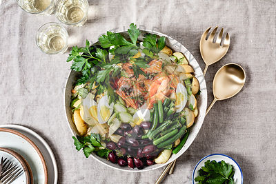 Salmon Nicoise salad on a neutral grey table cloth.