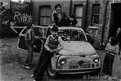 Children play with an abandoned car in Fieldgate Mansions