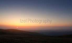 The pink, orange and blue skies of sunrise over Bampton Common from the summit of Rampsgill Head in the Lake Distict UK.
