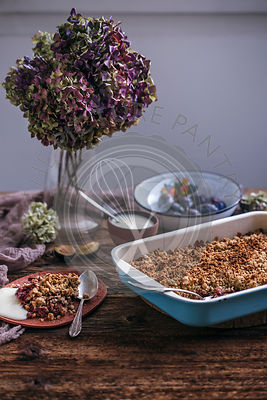 Plum crumble in a baking pan and served on a ceramic plate