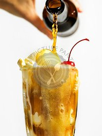 Pouring root beer into a float with vanilla ice cream and cherry.