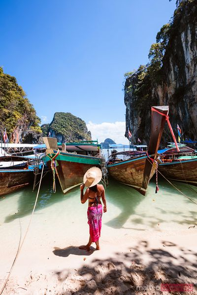 Woman with sarong standing near longtail boats, Krabi, Thailand