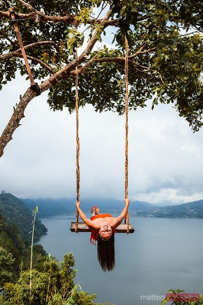 Woman enjoying a ride on a swing, Bali, Indonesia