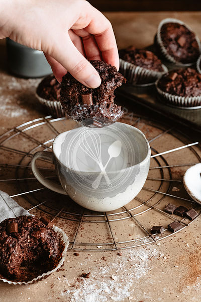 Dunking a chocolate  muffin into milk