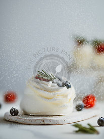 Sprinkles icing sugar on mini Pavlova cake with berries and rosemary