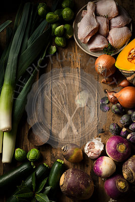 Raw winter vegetables and chicken being prepared for soup. They are displayed on a rustic timber background with a vintage ru...