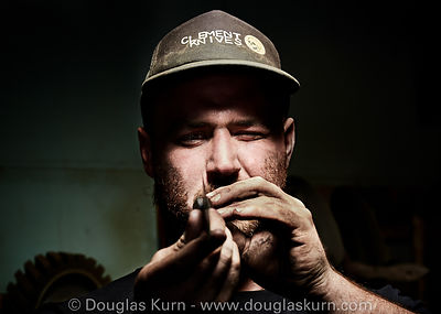 Environmental portrait of an artisan who hand makes knives in his riverside studio, by Douglas Kurn, photographer.